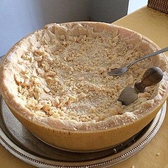 Parmigiano-Reggiano - Half a wheel of Parmigiano-Reggiano cheese carved with a Parmesan knife.