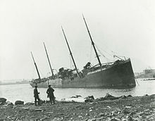 "Two men observe a large beached ship with ""Belgian Relief"" painted on its side"