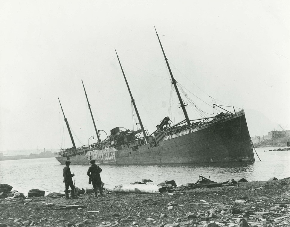 """Two men observe a large beached ship with """"Belgian Relief"""" painted on her side"""