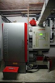 Holzhackschnitzelheizung der Fa. Hargassner, 45 kW, Hackschnitzelzufuhr durch quadratisches Rohr im Bild