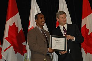 "Hassan Abdillahi - Hassan Abdillahi ""Karate"" being presented with a NEPMCC Media Award by Prime Minister Stephen Harper at Seneca College (2009)."
