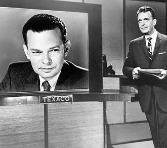 The Huntley–Brinkley Report - A promotional photo from June 1963 taken at NBC News' New York base. David Brinkley appears on the screen from Washington, while Chet Huntley is standing to the right.