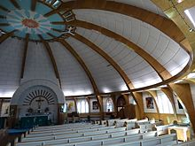 Wooden pews under a domed white ceiling with regular wooden vaults. Paintings and windows alternate along the walls