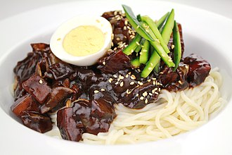 Jajangmyeon - Jajangmyeon topped with a hard-boiled egg, julienned cucumber, and toasted sesame seeds