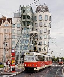 Un vieux tramway rouge et crème au premier plan devant un bâtiment très moderne de verre et de béton.