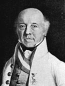 Black and white print of a bald man with his only hair a tuft at each ear. He wears a white military uniform with a high collar. The coat is open at the front, showing a vest underneath.