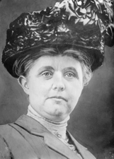 A black and white photograph of a woman wearing a large, decorative hat
