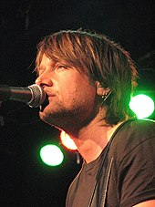 A brown-haired man singing into a microphone