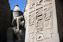 Surskribi hieroglifoj kovras obeliskon en malfono. Ŝtonstatuo estas en fono.