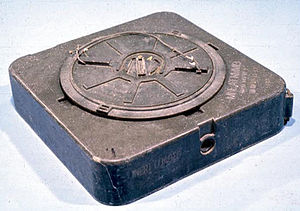 Anti-handling device - Side view of an M19 anti-tank mine, dating from the 1970s showing an additional fuze well on the side of the mine (sealing cap has been removed) designed for use with booby-trap firing devices. There is another empty fuze well (not visible) located underneath the mine