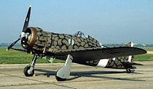 a single-engine monoplane with green and black mottled camouflage paint parked on the tarmac