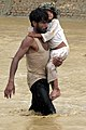 Man carries child to safety during a flood in Nari Shahi, Nangarhar, Afghanistan.jpg