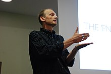 Photograph of Felleisen standing in front of a projector screen, gesturing