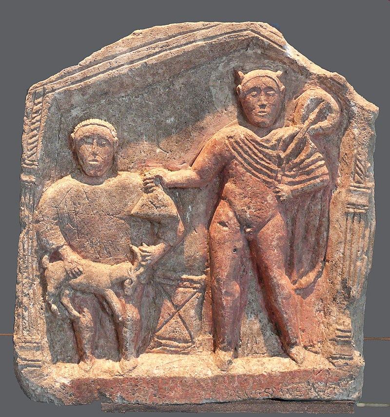 Crude stone relief carving of two standing male figures, facing the viewer and flanked by columns under a peaked roof; the taller figure is mostly nude and holds a bag or purse toward the shorter figure, who holds a goat by the horns