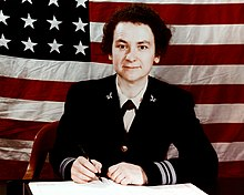 Female WAVE officer sitting at her desk in dress blue uniform