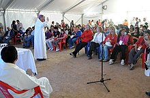 A color photo of a priest offering mass in a white tent with dirt floor for the workers and family members at San Jose Mine