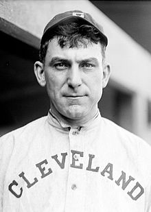 "A black-and-white photograph of a man in an old-style white baseball jersey reading ""Cleveland"" across the chest and dark cap"