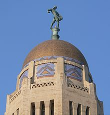 Gold-colored dome atop octagonal stone tower; stylized thunderbirds on sides of tower just below dome; bronze statue of someone sowing seed by hand on top