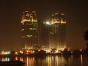 Orascom Construction Industries - Night view of the Nile City Towers. Orascom Construction  headquarters is at the south tower (on the right). In-between the two towers lies the Fairmont Hotels and Resorts.