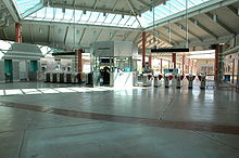 An empty entrance of a train station with many ticket machines located in a distance