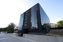 "A black glass cubic building with a sidewalk and low retaining wall with ""Exelon Pavilions"" on it in front."