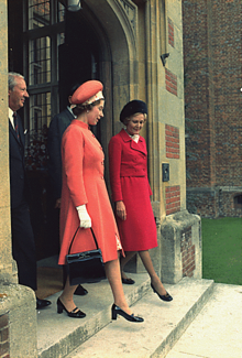 Elizabeth and Pat Nixon walk out of a red-brick building in step