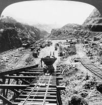 Large excavation through mountains, seen from a rail tunnel