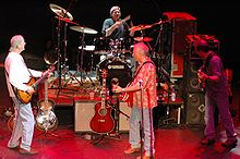A band is on a stage. The drummer sits behind a drumkit at the back. Three guitarists stand, facing away from the camera at the front.