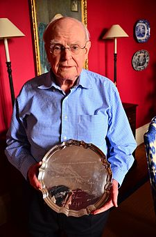 Professor Sid Watkins displays his tribute plate from the Formula One drivers of the 1985 season (6986945061).jpg