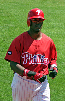 "A baseball player wearing a red cap with the letter ""P"" inscribed. His jersey is also red, and is inscribed with the word ""Phillies"". His pants are white with thin red stripes running vertically across."