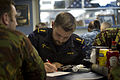 Royal New Zealand Navy Able Medic Finbar Marshall, center, fills out paperwork at a shipboard orientation aboard the amphibious dock landing ship USS Pearl Harbor (LSD 52) June 3, 2013, in Apia, Samoa, during 130603-N-WD757-069.jpg