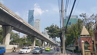 Sathon Road - Sathon Road in front of the Saint Louis Church, Bangkok, showing the elevated BTS skytrain track and Mahanakhon in the view