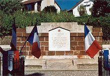 a low red brick memorial topped with a red star and flanked by French flags