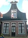 foto van Bakstenen huis voorzien van een klokgevel met gebroken fronton