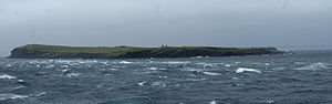 Stroma, Scotland -  alt=View of a low-lying island under grey skies, with rough water and cresting waves in the foreground