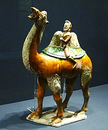A glazed figurine of a red camel, which is being ridden by a bearded merchant in green clothing