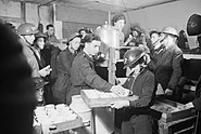 Tea and buns are supplied by local Air Raid Precautions (ARP) workers to fellow ARP workers and civilians in this basement shelter in South East London during 1940. D1623