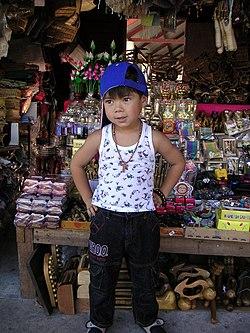 Enfant thaïlandais vendant des souvenirs, dernier maillon d'une chaîne de production pouvant s'étendre sur plusieurs pays.