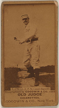 "A man in a striped cap, white baseball uniform with the words ""ST. LOUIS"" obscured on the front and black belt pretends to swing an imaginary bat."