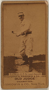 A sepia-toned image of a man wearing an old-style white baseball uniform and cap throwing a baseball