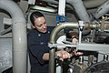 U.S. Navy Machinist's Mate 3rd Class Krystle Mott tightens a bolt after changing a water filter in the main engine room aboard the guided missile destroyer USS Stout (DDG 55) while in port at Naval Support 131212-N-UD469-122.jpg