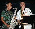 "US Navy 050622-N-7783B-007 Musician 3rd Class Jason Stark of the 7th Fleet Band, ""Orient Express"" plays alongside a Royal Thai Marine Band counterpart during a performance at the Singsamut Elementary School in Satt.jpg"
