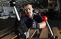 US Navy 050718-N-0413R-024 Storekeeper Seaman Miguel Rivera bands pallets together with a banding kit in the hangar bay aboard the nuclear-powered aircraft carrier USS Nimitz (CVN 68).jpg