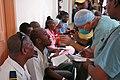 US Navy 070903-N-6020F-046 U.S. Public Health Service Capt. Angel Rodriguez-Espada, attached to Military Sealift Command hospital ship USNS Comfort (T-AH 20), screens patients at Centre Hospitalier Eliazar Germain in Pétion-Ville.jpg