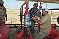 US Navy 080722-A-3155B-034 Cmdr. Doug Kunzman, assigned to the embedded provincial reconstruction team in Al Anbar province, Iraq, watches as senior local engineer Ali Wesam checks the valve function on the distribution system.jpg