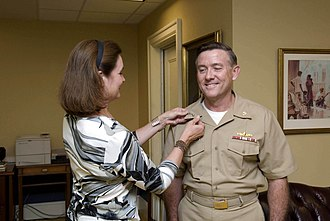 Bruce E. MacDonald - Vice Adm. Judge Advocate General (JAG) Bruce MacDonald is pinned by his wife, Karen, during a promotion ceremony at the Pentagon. MacDonald is the first Vice Adm. JAG in the Navy. The 2008 National Defense Authorization Act advanced the position of the JAG in the Navy, Army, and Air Force to the grade of a three-star general or flag officer. (U.S. Navy photo by Mass Communication Specialist 1st Class Tiffini M. Jones/Released)