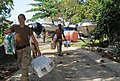 US Navy 100127-N-1831S-110 Gunner's Mate 3rd Class Kristen Luna, assigned to Beach Master Unit (BMU) 2, carries baby supplies to the Killick Haitian Coast Guard Base during a humanitarian supply delivery.jpg