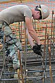 US Navy 100928-N-3887D-114 Petty Officer 3rd Class Joshua Frisbee ties rebar cages to be placed in the ground for the construction of a youth facil.jpg