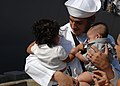 US Navy 110727-N-YF783-055 Damage Controlman 3rd Class Marc Cendejas holds his four-month-old son for the first time, along with his daughter, afte.jpg