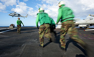 US Navy 120212-N-OY799-225 Sailors run to move cargo on the flight deck during a vertical replenishment aboard the Nimitz-class aircraft carrier US.jpg